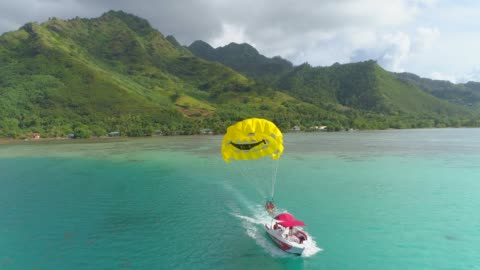 aerial drone view of a man and woman couple parasailing tandem over a tropical island. - french polynesia stock videos & royalty-free footage