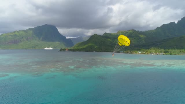 aerial drone view of a man and woman couple parasailing tandem over a tropical island near a cruise ship. - kite sailing stock videos & royalty-free footage