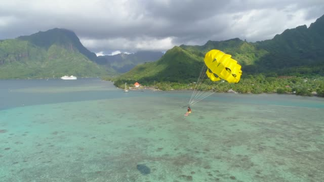 Aerial drone view of a man and woman couple parasailing tandem over a tropical island near a cruise ship.