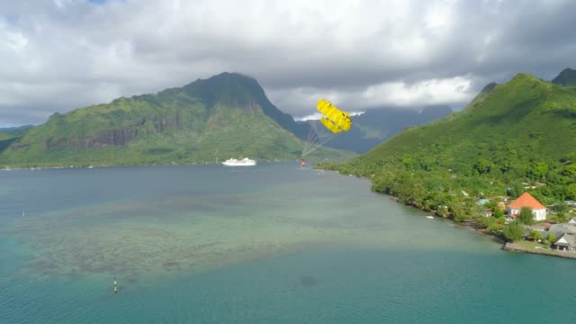 aerial drone view of a man and woman couple parasailing tandem over a tropical island near a cruise ship. - french polynesia stock videos & royalty-free footage