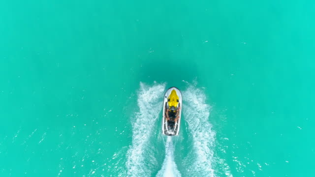 aerial drone view of a man and woman couple riding a jet ski waverunner personal watercraft in bora bora tropical island. - jet ski stock videos & royalty-free footage