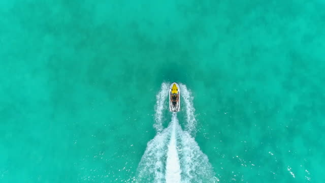 aerial drone view of a man and woman couple riding a jet ski waverunner personal watercraft in bora bora tropical island. - bora bora aerial stock videos and b-roll footage