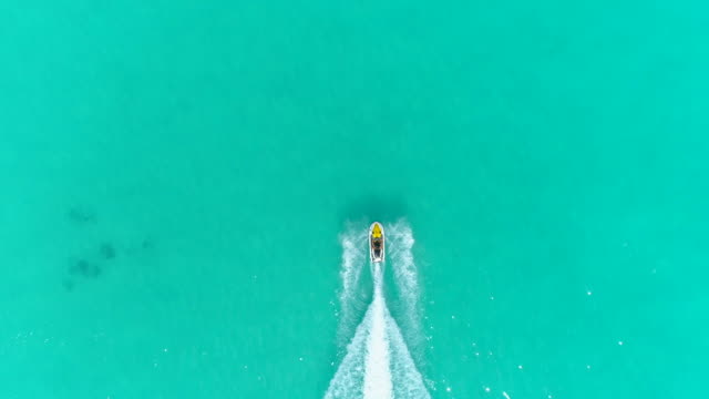 aerial drone view of a man and woman couple riding a jet ski waverunner personal watercraft in bora bora tropical island. - idyllic video stock e b–roll