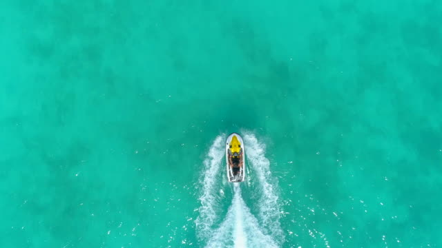 aerial drone view of a man and woman couple riding a jet ski waverunner personal watercraft in bora bora tropical island. - time-lapse - jet ski stock videos & royalty-free footage
