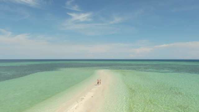 vídeos de stock, filmes e b-roll de aerial drone view of a man and woman couple running on a sandbar tropical island in over water bungalow hotel resort. - exotismo