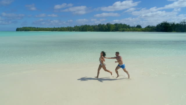 Aerial drone view of a man and woman couple running playfully on a scenic tropical island in French Polynesia.