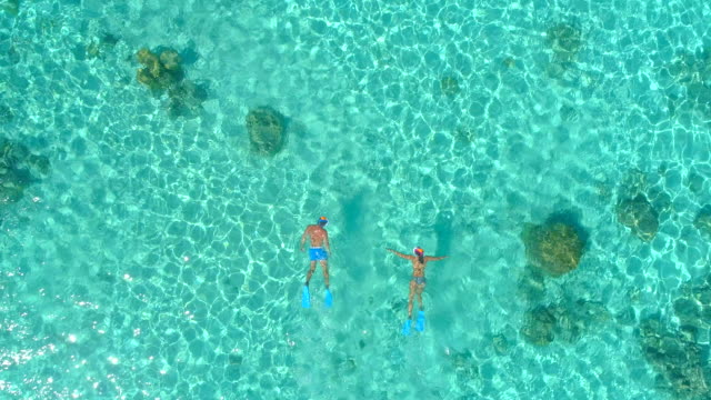Aerial drone view of a man and woman couple snorkeling swimming around scenic tropical islands.