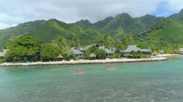 aerial drone view of a man and woman couple sup stand up paddle boarding at a resort on a tropical island. - フランス海外領点の映像素材/bロール