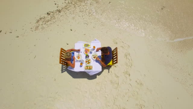 aerial drone view of a man and woman eating breakfast on a tropical island sandbar beach. - seat stock videos & royalty-free footage