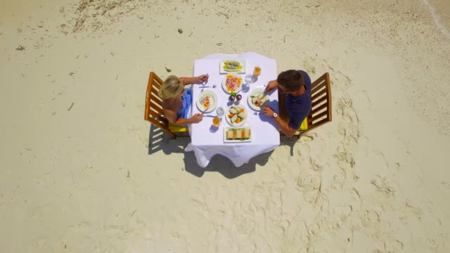 vídeos y material grabado en eventos de stock de aerial drone view of a man and woman eating breakfast on a tropical island sandbar beach. - top garment