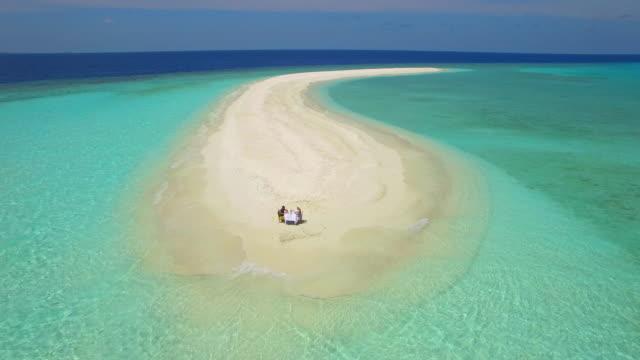 Aerial drone view of a man and woman eating breakfast on a tropical island sandbar beach.