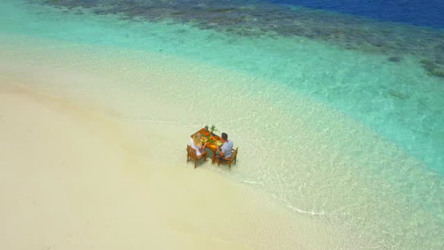 aerial drone view of a man and woman eating breakfast on a tropical island beach. - goodsportvideo stock videos and b-roll footage