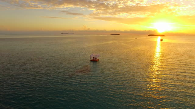 stockvideo's en b-roll-footage met aerial drone view of a man and woman having dinner on a floating raft boat at sunset. - decoraties