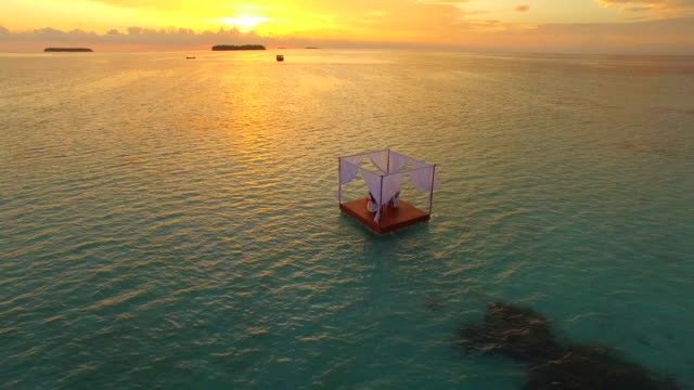 Aerial drone view of a man and woman having dinner on a floating raft boat at sunset.