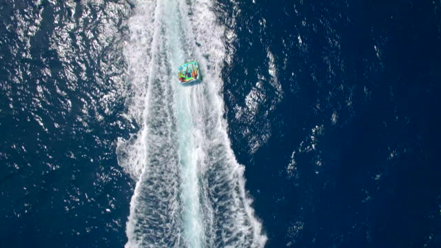 vidéos et rushes de aerial drone view of a man and woman on an inflatable tube towing behind a boat to a tropical island. - tirer