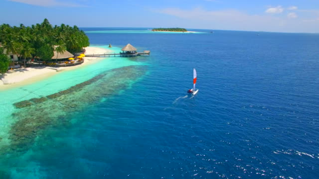 Aerial drone view of a man and woman sailing on a boat to a tropical island.