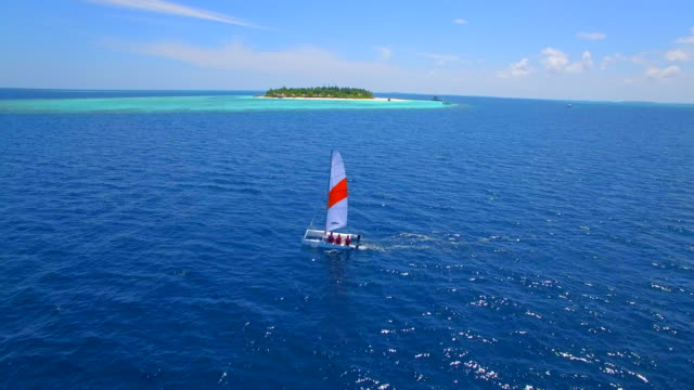 aerial drone view of a man and woman sailing on a boat to a tropical island. - 島点の映像素材/bロール
