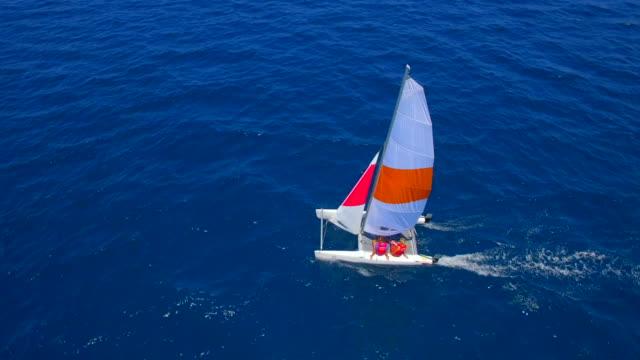 vídeos de stock e filmes b-roll de aerial drone view of a man and woman sailing on a boat to a tropical island. - vela peça de embarcação