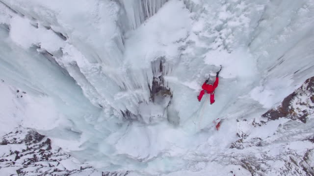 vidéos et rushes de aerial drone view of a man ice climbing on a frozen waterfall in the mountains. - glacé