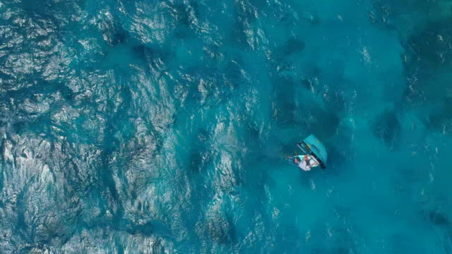 aerial drone view of a man kite board wing surfing hydrofoiling over a coral reef in the pacific ocean. - south pacific ocean stock videos & royalty-free footage