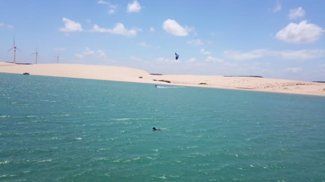 Aerial drone view of a man kiteboarding on a kite board in a lagoon lake.