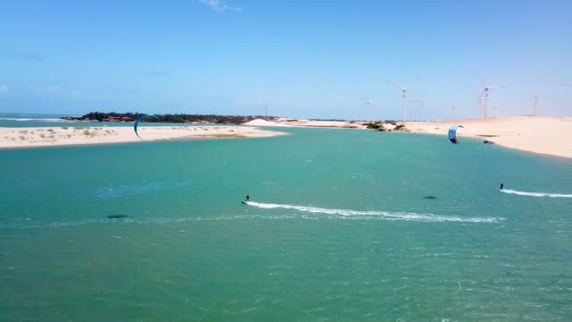 aerial drone view of a man kiteboarding on a kite board in a lagoon lake. - lagoon stock videos & royalty-free footage