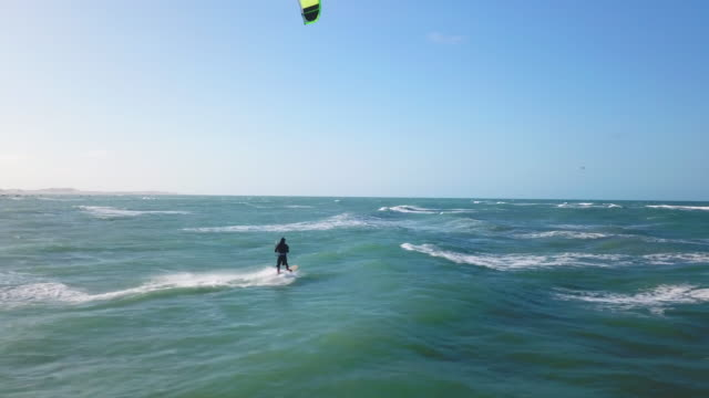 Aerial drone view of a man kiteboarding on a kite board.