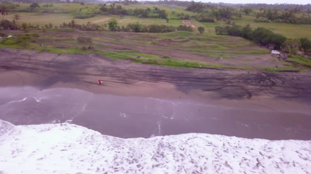 Aerial drone view of a man riding his motocross motorcycle on the beach.