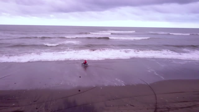 aerial drone view of a man riding his motocross motorcycle on the beach. - one teenage boy only stock videos and b-roll footage