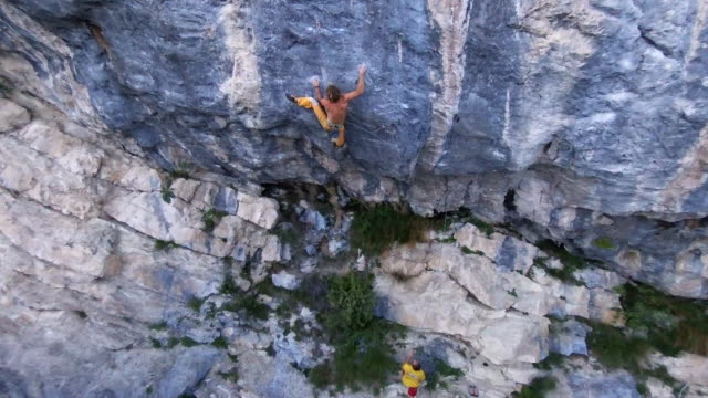 Aerial drone view of a man rock climbing up a mountain.