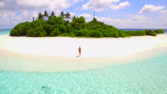 Aerial drone view of a man running, diving in and swimming on a small deserted tropical island.