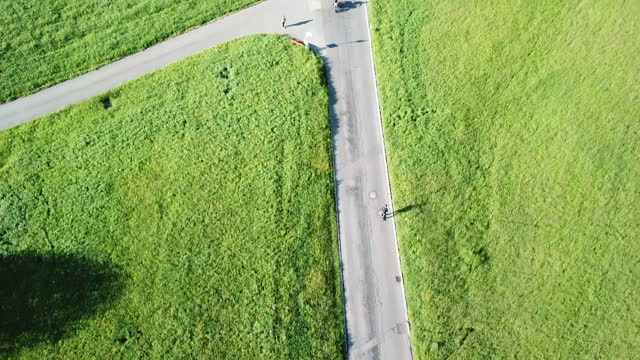 vidéos et rushes de aerial drone view of a man skateboarding on a rural country road in switzerland. - slow motion - adulte d'âge moyen