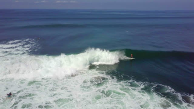 Aerial drone view of a man surfing on a wave in Indonesia.
