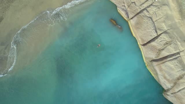 vídeos y material grabado en eventos de stock de aerial drone view of a man swimming in a blue green ocean bay sea. - bahía