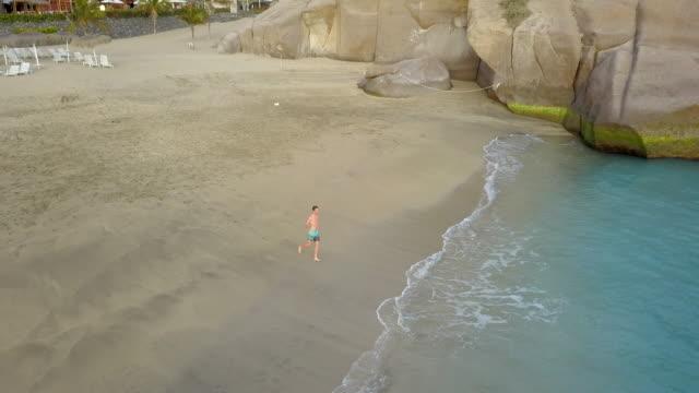 vídeos de stock, filmes e b-roll de aerial drone view of a man walking to the ocean and swimming in a bay sea. - baía