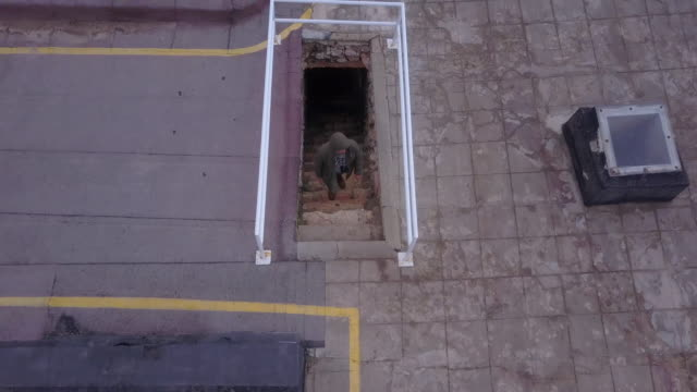 Aerial drone view of a man walking up stairs stairway to a rooftop.