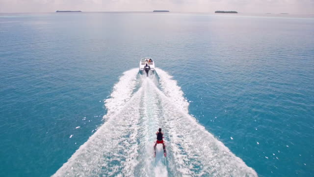 vidéos et rushes de aerial drone view of a man water skiing near a tropical island. - luxe