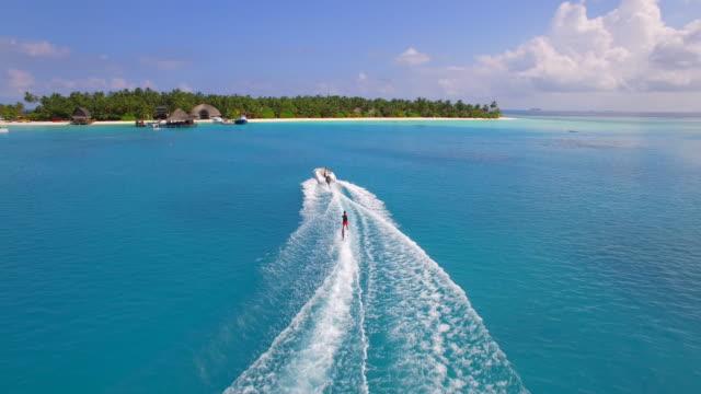 vídeos de stock e filmes b-roll de aerial drone view of a man water skiing near a tropical island. - barco a motor embarcação de lazer