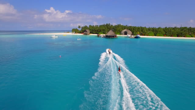 vídeos de stock, filmes e b-roll de aerial drone view of a man water skiing near a tropical island. - oceano índico