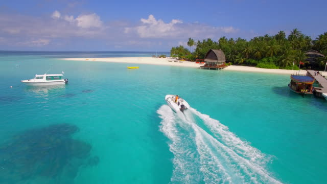 aerial drone view of a man water skiing near a tropical island. - top garment stock videos & royalty-free footage