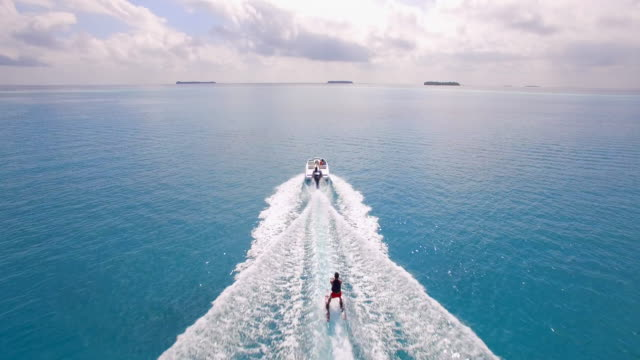 aerial drone view of a man water skiing near a tropical island. - 航跡点の映像素材/bロール