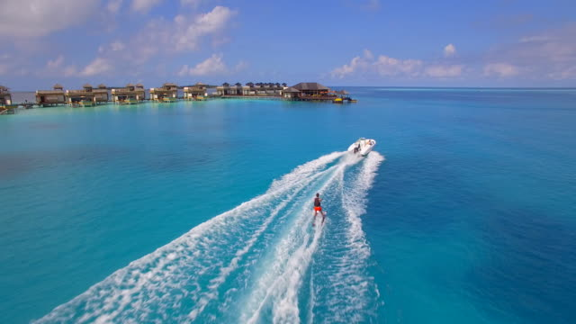 aerial drone view of a man water skiing near a tropical island. - speed boat stock videos & royalty-free footage