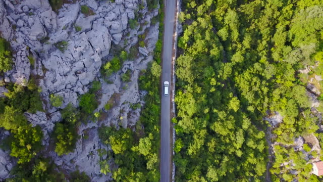 aerial drone view of a minivan car vehicle driving on a rural road. - van stock videos & royalty-free footage