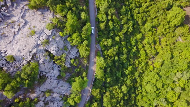 aerial drone view of a minivan car vehicle driving on a rural road. - montenegro stock videos & royalty-free footage