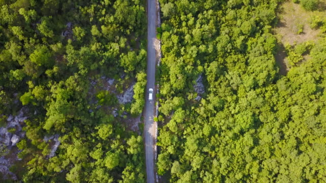 aerial drone view of a minivan car vehicle driving on a rural road. - car stock videos & royalty-free footage