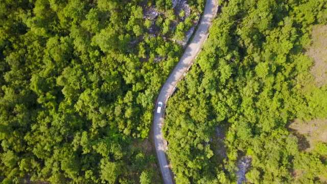 vídeos y material grabado en eventos de stock de aerial drone view of a minivan car vehicle driving on a rural road. - vehículo terrestre