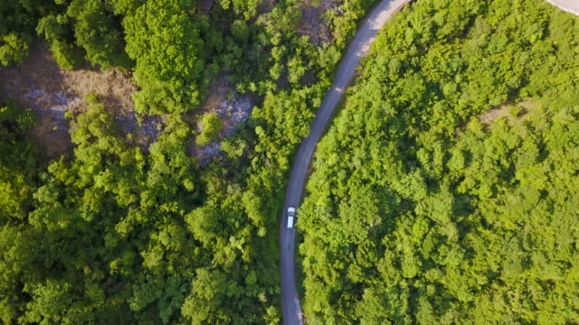 aerial drone view of a minivan car vehicle driving on a rural road. - berufsfahrer stock-videos und b-roll-filmmaterial