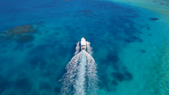aerial drone view of a motor boat going to a scenic tropical island in the maldives. - wide shot stock videos & royalty-free footage