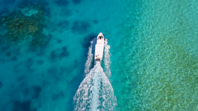 aerial drone view of a motor boat going to a scenic tropical island in the maldives. - motorboot stock-videos und b-roll-filmmaterial