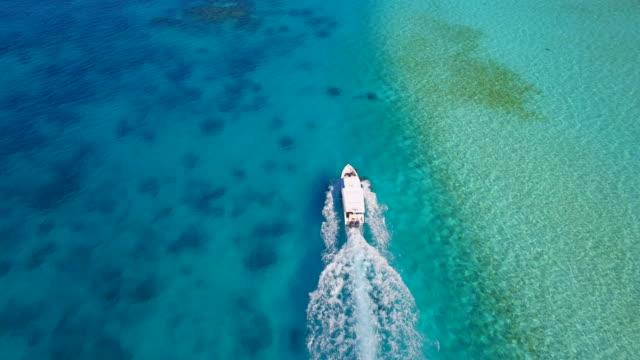 vídeos de stock e filmes b-roll de aerial drone view of a motor boat going to a scenic tropical island in the maldives. - barco a motor embarcação de lazer